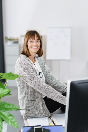 small office: Cheerful Office Woman Sitting on her Desk with Documents and Smiling at the Camera.