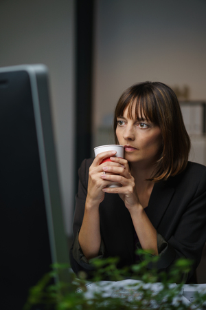 energising: Businesswoman Holding a Cup of Drink, Looking at her Computer Screen Seriously While Reading Something.
