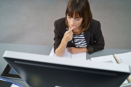 high angle view: High Angle View of a Pensive Businesswoman Facing her Computer Monitor on her Desk.