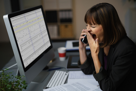 Tired Businessman at her Desk, Showing Yawning Gesture While Talking to Someone on Mobile Phone. Stockfoto