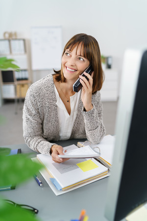 interrupted: Businesswoman smiling as she takes a phone call that has interrupted her working on documents and paperwork at her desk Stock Photo