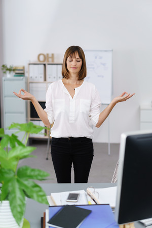 business mind: Businesswoman standing meditating in her office with her eyes closed and a tranquil expression on her face Stock Photo