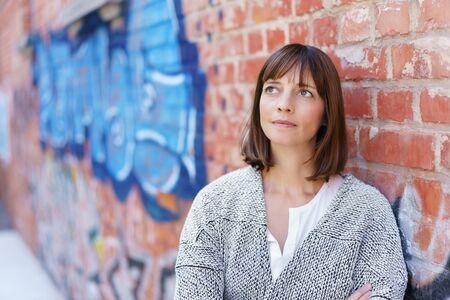 wistful: Pensive Adult Woman Looking Up While Leaning Against Brick Wall. Stock Photo