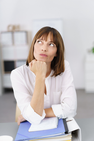 introspective: Thoughtful Businesswoman Leaning on her Desk with Hand on her Chin and Looking Up.