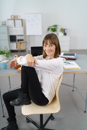 Happy Office Woman Sitting on her Chair with Knee Up and Smiling at the Camera.