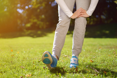 suppleness: Lower Body Shot of a Healthy Woman Stretching her Legs at the Park at Early in the Morning. Stock Photo