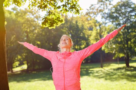tilted: Happy Healthy Woman Opening her Arms Wide While Listening to Music Through Earphones at the Park.