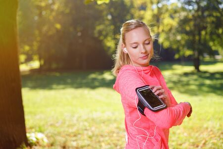 outdoor exercise: Healthy Young Woman Looking at her Mobile Phone on her Arm While Listening to Music Through Earphones After her Outdoor Exercise at the Park.