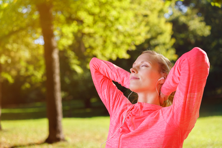 quietude: Attractive young woman enjoying her music relaxing outdoors in the garden with her hands clasped behind her head and eyes closed in bliss