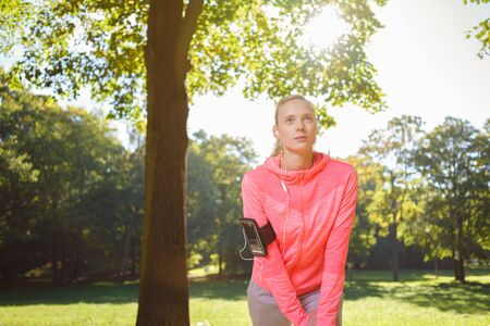 limbering: Three Quarter Shot of a Determined Woman Having a Warm Up Exercise at the Park Early in the Morning