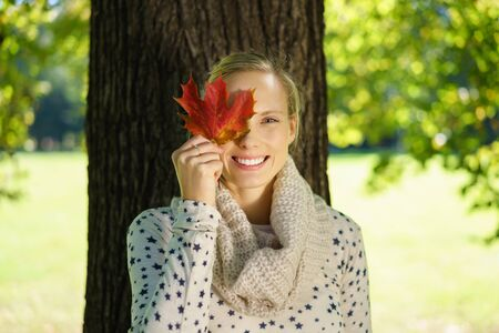 concealing: Half Body Shot of a Pretty Young Woman Holding an Autumn Leaf Over her Eye and Smiling at the Camera Against Huge Tree Trunk at the Park.