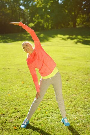 limbering: Full body Shot of a Healthy Young Woman Doing Body Stretching Exercise at the Park at Early in the Morning.