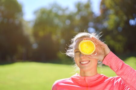 concealing: Healthy Young Woman Holding a Fresh Orange Slice Over her Eye and Smiling at the Camera at the Park. Stock Photo