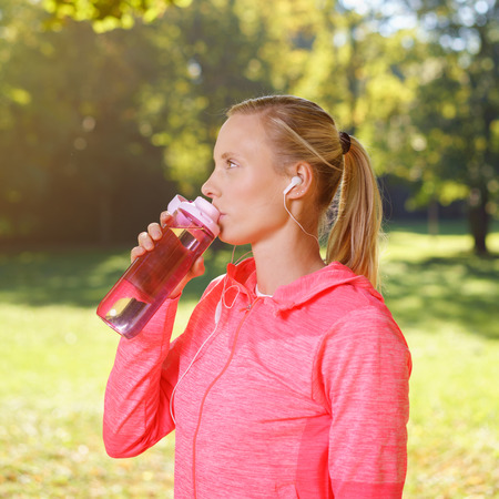 downloaded: Half Body Shot of a Pretty Young Woman Drinking Water After an Outdoor Exercise at the Park.