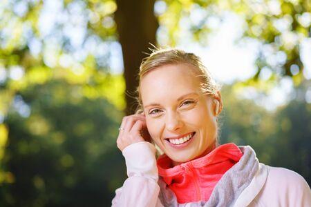 rubia: Bastante joven mujer rubia, escuchar música en un auricular mirando a la cámara con una sonrisa radiante de alegría del placer