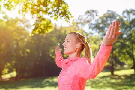 éxtasis: Pensativo mujer joven escucha música en los auriculares con los brazos abiertos mientras se hace un ejercicio al aire libre.