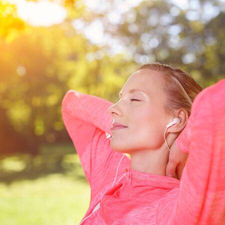 �xtasis: Mujer joven que sonr�e de felicidad mientras se relaja al aire libre en la luz del sol caliente que escucha la m�sica en sus auriculares que se sientan con la cabeza inclinada hacia atr�s, los ojos cerrados y una sonrisa de �xtasis
