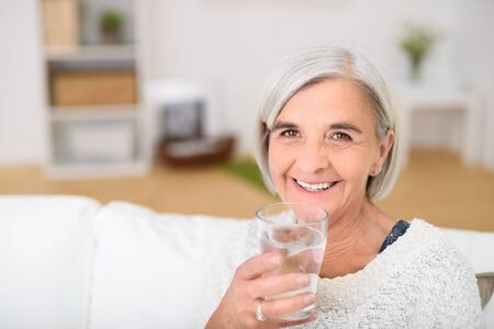 Close up Senior Woman Sitting at the Couch, Holding a Glass of Water and Smiling at the Camera. Imagens