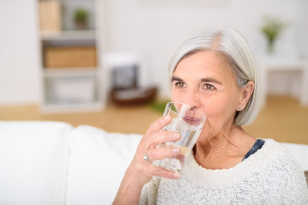 Close up Middle Aged Woman Drinking a Glass of Water at the Living Room and Looking Into the Distance. Stock Photo