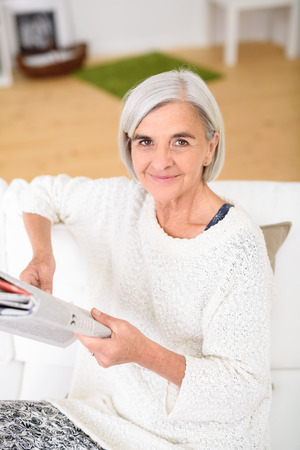 Portrait of a Senior Woman Holding a Magazine at the Living Room Couch, Smiling at the Camera Stock Photo