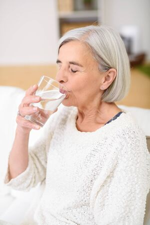 sediento: Primer plano Sediento mayor de la mujer que bebe un vaso de agua en la sala de estar con los ojos cerrados.