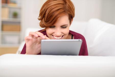 persona feliz: Navegación Mujer bonita en una tableta mientras se encuentra relajado en un sofá en casa sonriendo con placer mientras navega el Internet Foto de archivo