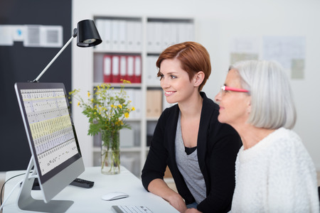 Young and Senior Office Women Working on the Computer Inside the Office. Stock Photo