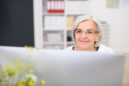 cabello corto: Gray-Haired Empresaria mayor que se sienta en ella, leyendo algo en su computadora de escritorio del monitor