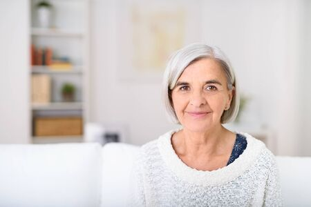 gray haired: Portrait of a Gray Haired Senior Woman Sitting at the Living Room, Smiling at the Camera