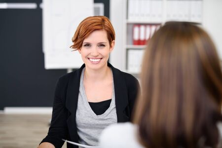 one on one meeting: Pretty Young Office Woman Smiling at the Camera While Having a One on One Meeting with her Colleague.