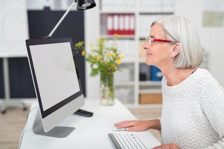 Glückliche ältere Office-Frau auf den leeren Bildschirm, während auf ihrem Computer an ihrem Arbeitstisch im Büro.