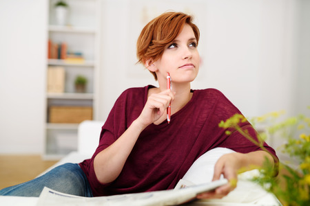 decision: Thoughtful Attractive Young Woman Answering Crossword Puzzle Game on Newspaper at the Living Room Couch.