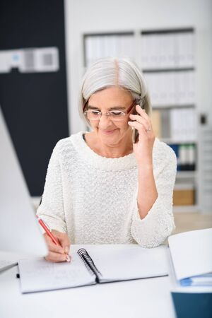 woman in office: Middle Aged Businesswoman Sitting at her and Writing Something While Talking to Someone on her Mobile Phone.