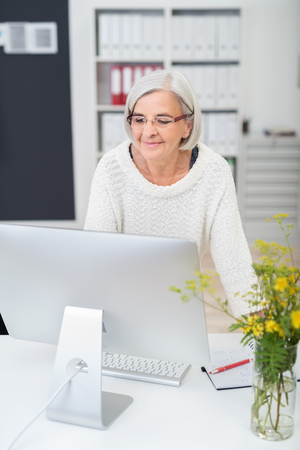 gray haired: Gray Haired Senior Office Woman Leaning on her Table While Reading Something on her Computer Monitor. Stock Photo