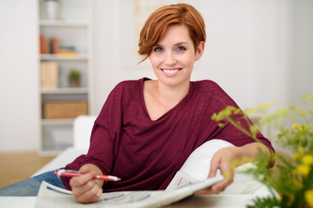 crossword puzzle: Smiling Pretty Young Woman Holding Newspaper and Pen While Relaxing at the Couch in the Living Room.