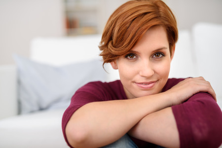 contented: Close up Pretty Young Woman Leaning her Chin on her Crossed Arms and Smiling at the Camera. Stock Photo
