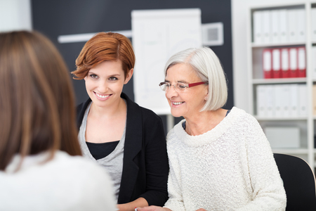 friendly: Three Office Women Having a Meeting at the Table Inside the Office. Stock Photo