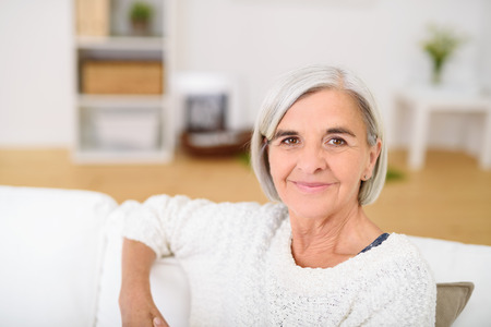 gray haired: Close Gray Haired Senior Woman Relaxing at the Living Room Couch and Smiling at the Camera.
