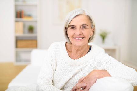 gray haired: Close up Gray Haired Middle Aged Woman Sitting on the Sofa and Smiling at the Camera.