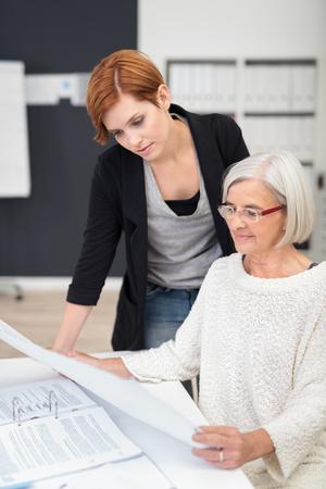 personas trabajando: Documentos de mediana edad y joven Oficina mujeres lectura de negocios en la mesa dentro de la Oficina. Foto de archivo