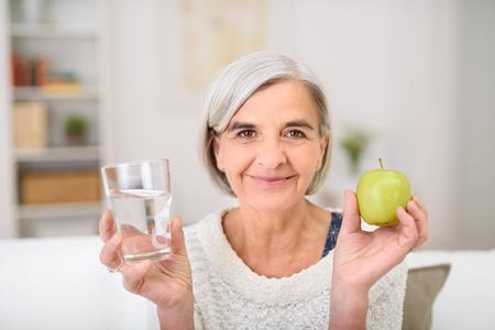 카메라에 물 미소의 회색 머리 수석 여자 유리와 신선한 그린 애플의 초상화,