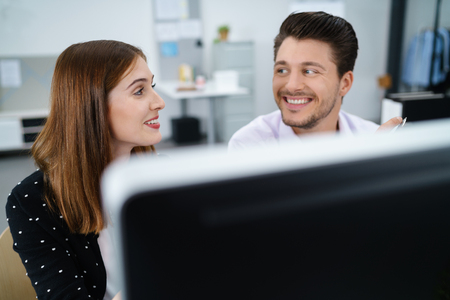 sat: two happy businesspeople smiling and talking at the office Stock Photo