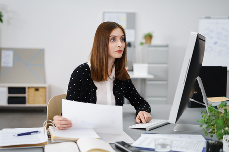 absorbed: Attractive businesswoman reading information on a desktop monitor with a serious absorbed expression as she holds a paper document in her hand