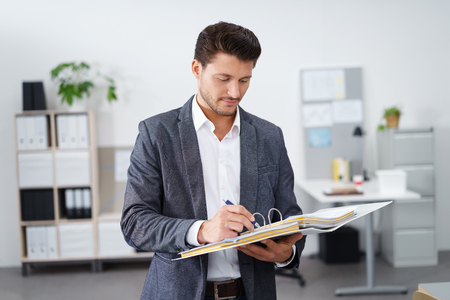 businessman standing at the office and writing in a folder