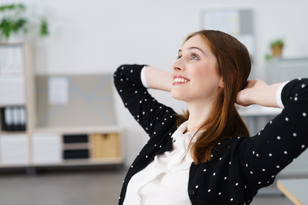 woman in office: Thoughtful Young Office Woman Sitting at her Table with Hands Holding the Back of her Head and Looking Up with Happy Facial Expression.