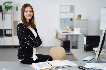 personal assistant: Attractive Young Businesswoman Sitting on her Desk Inside the Office and Smiling at the Camera with Arms Crossing Over her Chest. Stock Photo
