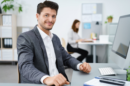 observant: manager sitting at desk and working on computer with co-worker in background