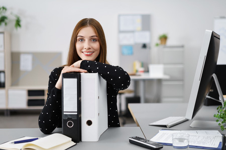 relaxed businesswoman leaning on black and white folders Stock Photo