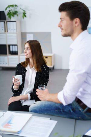 2 つのビジネス部門の同僚、男、魅力的なスタイリッシュな若い女性、彼らはコーヒーを飲みながらリラックス フレーム ウィットの丁寧な表現の左