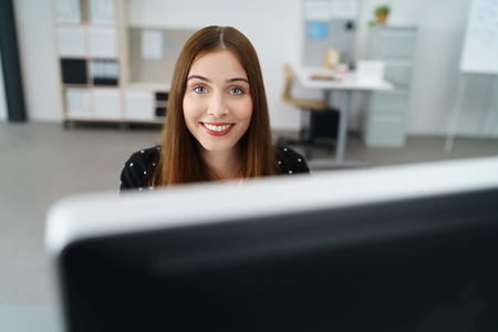 looking at computer: smiling woman looking over computer screen at work Stock Photo